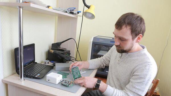 Степан Еньшин, инженер лаборатории Медицинская инженерия, в руках у него у него разработанный учеными аппаратно-программный комплекс для измерения микропотенциалов сердца (без сенсоров)