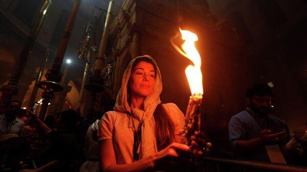Православные верующие c Благодатным огнем в Храме Гроба Господня в Иерусалиме