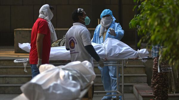 Подготовка тел погибших к кремации жертв пандемии в Дели
