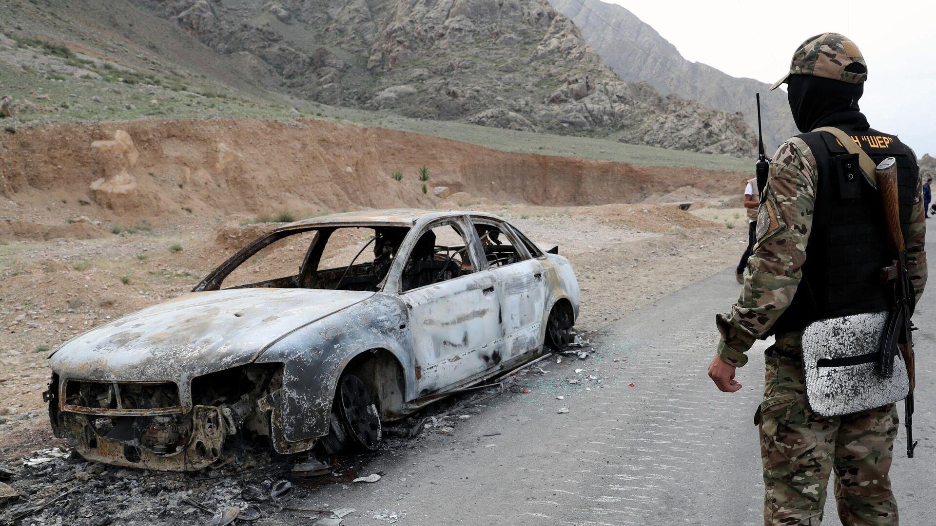 Военнослужащий Киргизии стоит у сгоревшей машины на границе Таджикистана и Киргизии в селе Кок-Таш - РИА Новости, 1920, 05.05.2021
