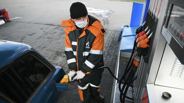 Заправщик заправляет автомобиль на АЗС Газпромнефть в Москве