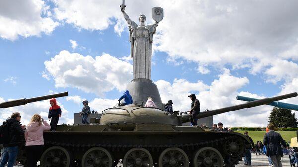 Люди возле скульптурной композицияи Родина-мать во время празднования 76-й годовщины Победы в Великой Отечественной войне у памятника Вечной Славы в Киеве