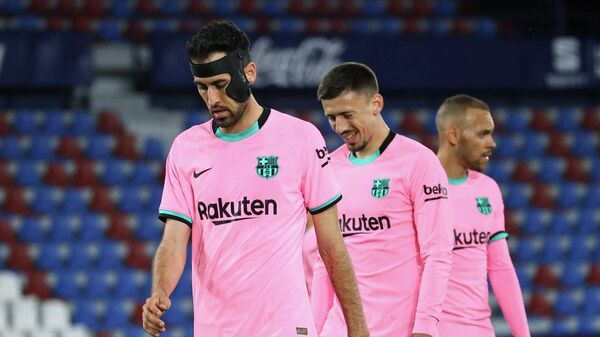 Barcelona's Spanish midfielder Sergio Busquets, Barcelona's French defender Clement Lenglet and Barcelona's Danish forward Martin Braithwaite react at the end of the Spanish league football match Levante UD against FC Barcelona at the Ciutat de Valencia stadium in Valencia on May 11, 2021. (Photo by JOSE JORDAN / AFP)