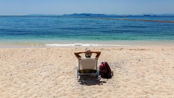 Отдыхающий на городском пляже Алимос в пригороде Афин