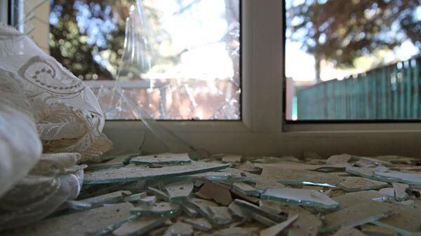 Разбитое окно дома, поврежденное разрывом снаряда в результате обстрела в Петровском районе Донецка