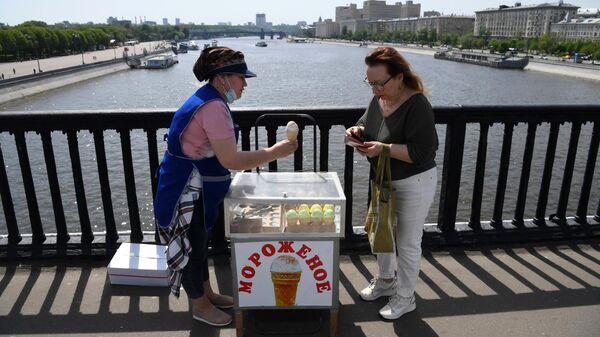 Женщина покупает мороженое на Крымском мосту в Москве