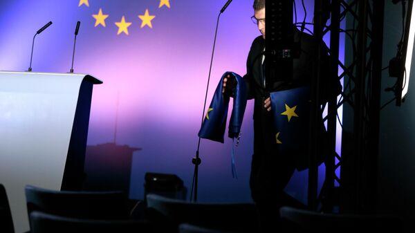 Сотрудник службы протокола с флагами ЕС в штаб-квартире Евросоюза в Брюсселе