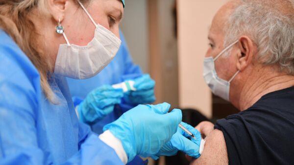 Медик прививает мужчину от коронавирусной инфекции COVID-19 российским препаратом Sputnik V в больнице в Сухуме
