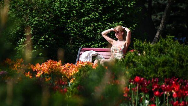 Девушка отдыхает под солнцем на скамейке в парке в Москве в жаркую погоду