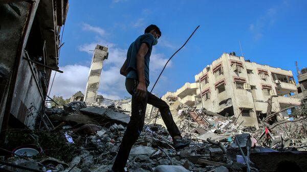 Молодой человек на месте разрушенных в результате бомбардировки зданий в секторе Газа
