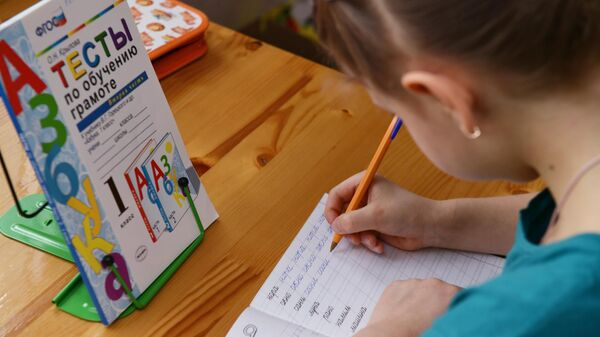 Ученица 1-го класса московской школы № 1376 на удалённом занятии по русскому языку у себя дома в Москве