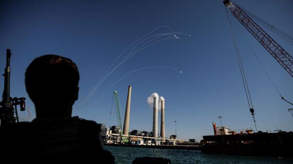 Израильский солдат наблюдает за перехватом ракет, выпущенных из сектора Газа