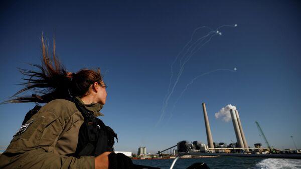 Израильский военный наблюдает за перехватом ракет, выпущенных из сектора Газа
