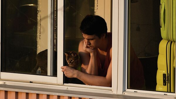 Молодой человек на балконе многоквартирного дома в Москве