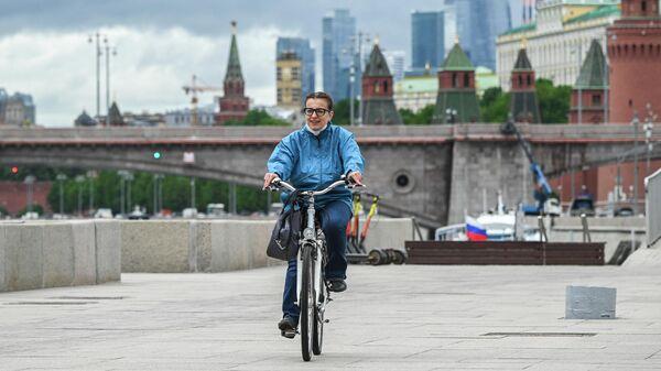 Девушка едет на велосипеде по Москворецкой набережной в Москве