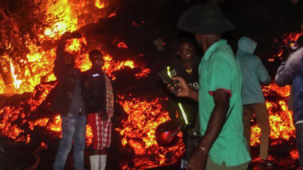Местные жители фотографируются на фоне лавы во время извержения вулкана Ньирагонго в Демократической республике Конго