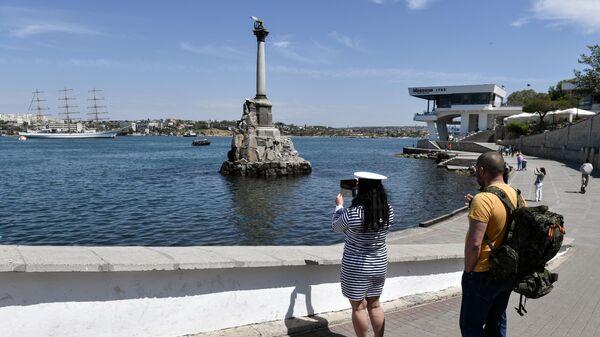 Девушка фотографирует памятник затопленным кораблям в Севастополе