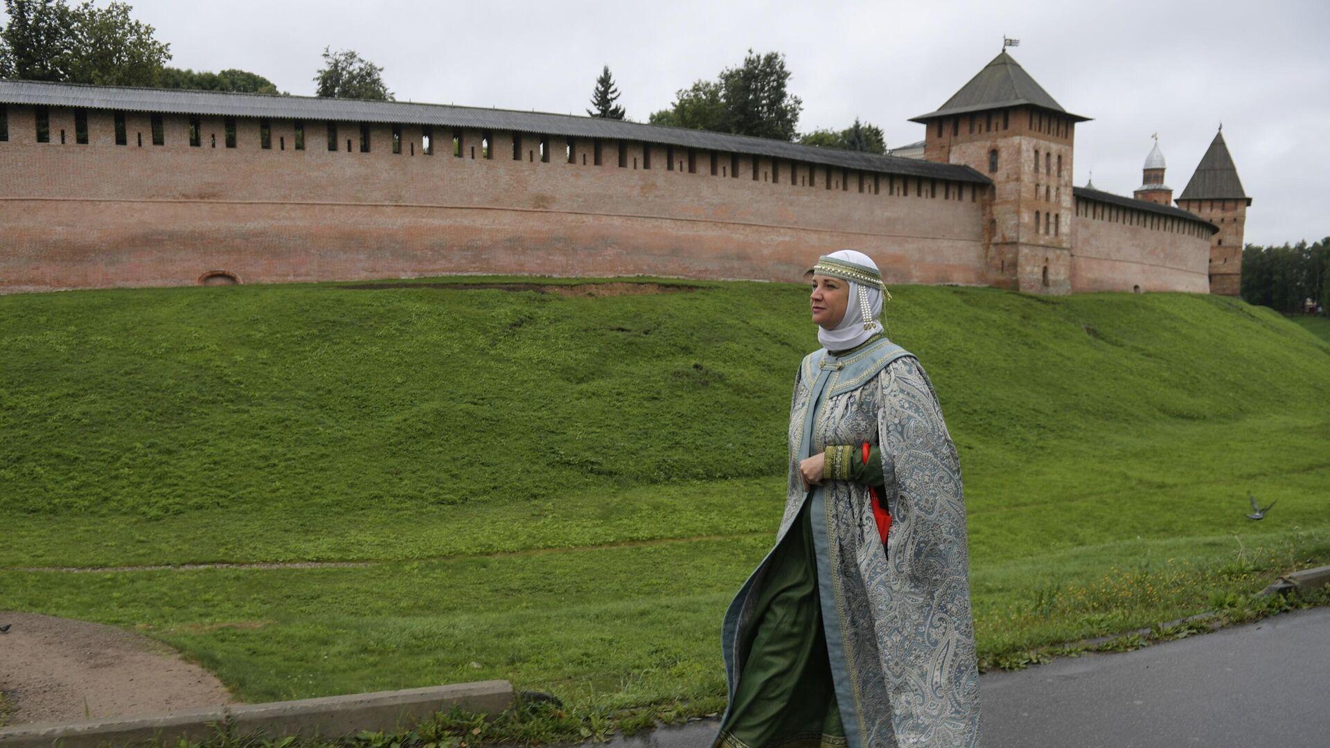 Экскурсовод в традиционной русской одежде на фоне Кремля в Великом Новгороде - РИА Новости, 1920, 28.05.2021
