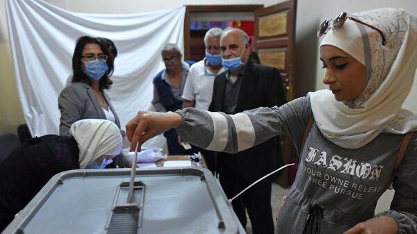 Девушка голосует на выборах президента Сирии на одном из избирательных участков Дамаска