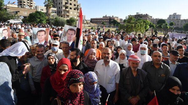 Люди у одного из избирательных участков Дамаска, где проходит голосование на выборах президента Сирии