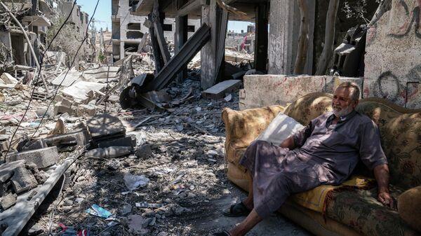 Житель Газы на улице, поврежденной в результате бомбардировки в секторе Газа