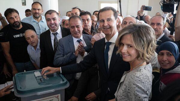 Башар Асад опускает бюллетень в урну во время выборов президента Сирии