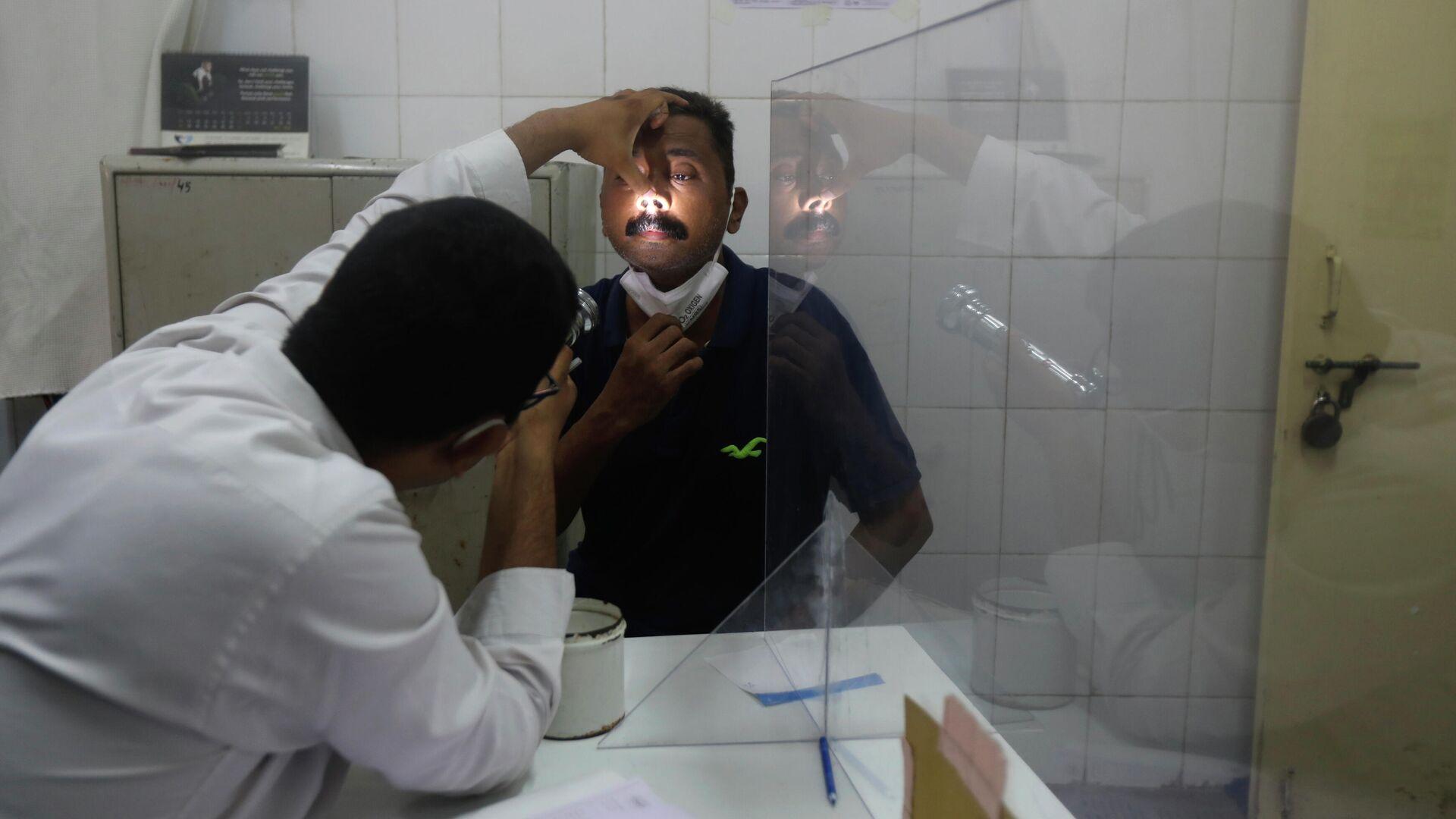 Врач осматривает мужчину на предмет симптомов мукормикоза в больнице Мумбаи в Индии - РИА Новости, 1920, 11.06.2021