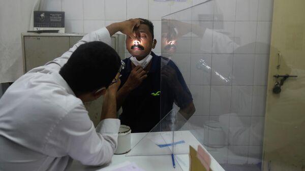 Врач осматривает мужчину на предмет симптомов мукормикоза в больнице Мумбаи в Индии