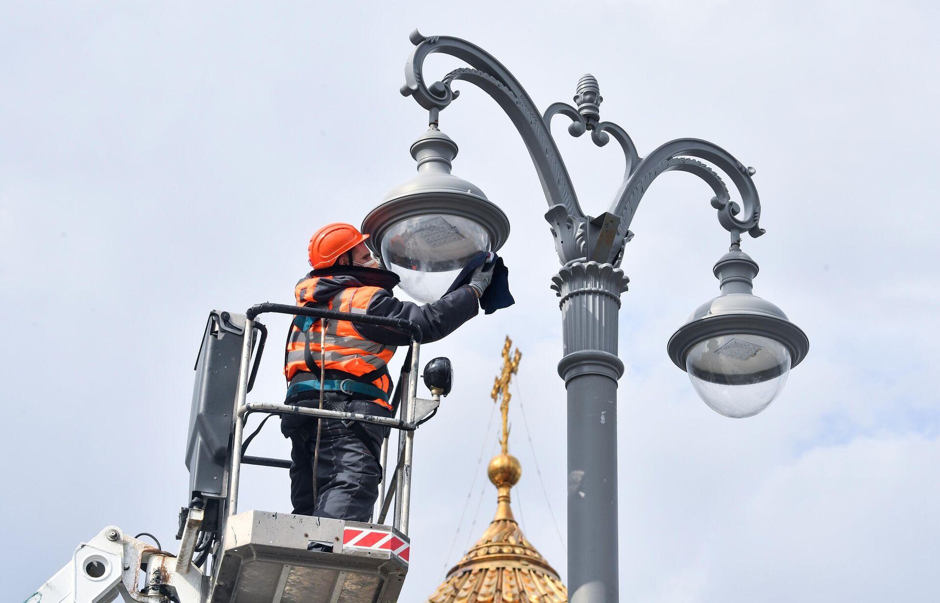 Сотрудник коммунальной службы протирает плафон фонаря наружного освещения на Пречистенской набережной в Москве - РИА Новости, 1920, 28.05.2021