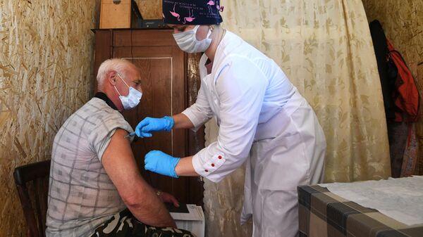 Пациент во время проведения выездной вакцинации от коронавирусной инфекции в дачном обществе Березка под Новосибирском