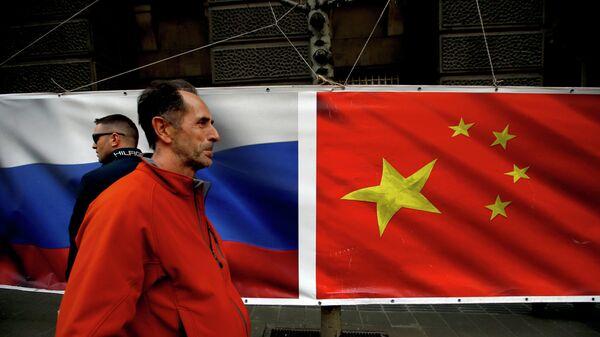 Люди проходят на фоне флагов России и Китая