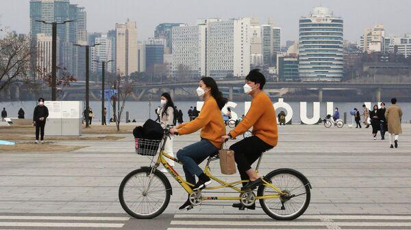 Пара катается на тандеме в парке в Сеуле, Южная Корея