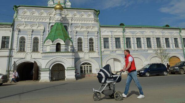 Мужчина с детской коляской идет по набережной Северной Двины у Архангельского подворья Спасо-Преображенского Соловецкого монастыря
