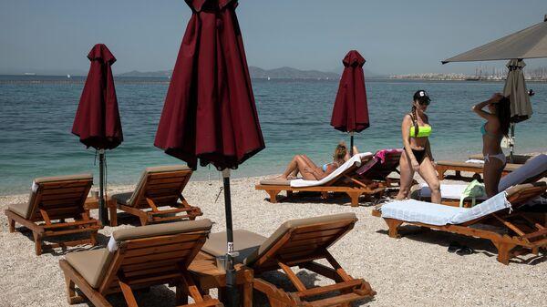 Люди на пляже в пригороде Алимос, Греция