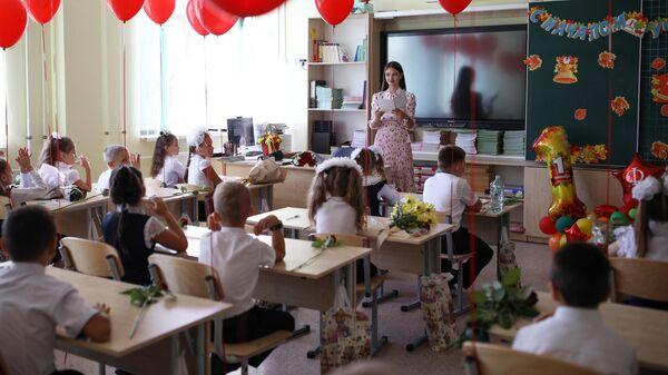 Первоклассники сидят за партой в классе в школе №71 в День знаний в Краснодаре