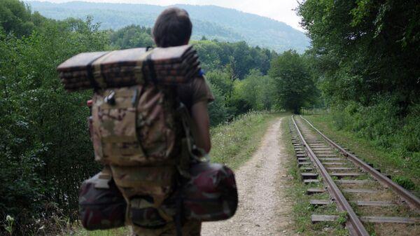 Турист идет вдоль узкоколейной железной дороги