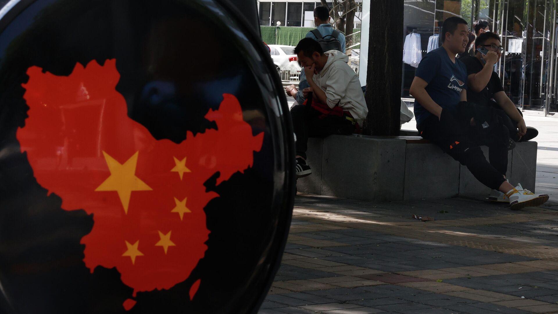 Жители отдыхают возле карты Китая возле торгового района в Пекине - РИА Новости, 1920, 26.07.2021