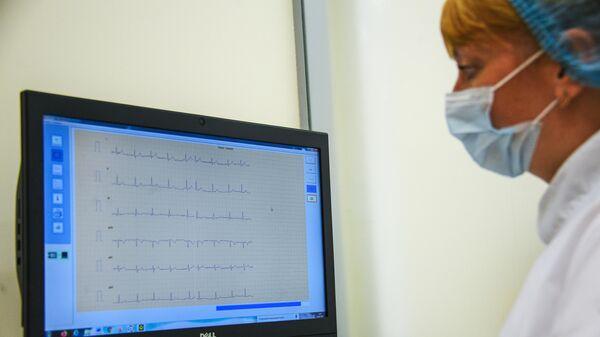 Врач смотрит на электрокардиографию