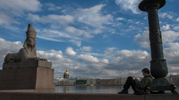 Молодой человек рисует на Университетской набережной в Санкт-Петербурге. Евгения Новоженина / РИА Новости