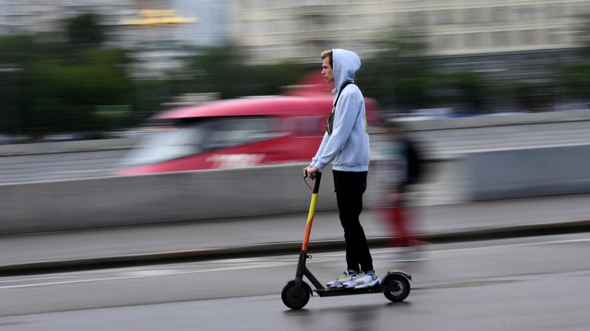 Молодой человек едет на электросамокате в центре Москвы - РИА Новости, 1920, 17.06.2021