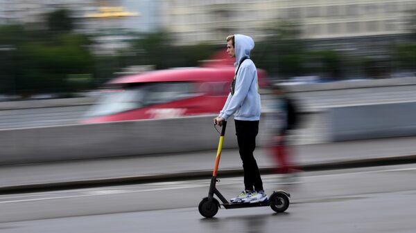 Молодой человек едет на электросамокате в центре Москвы
