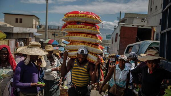 Мужчина несет товары на уличном рынке в Порт-о-Пренсе, Гаити