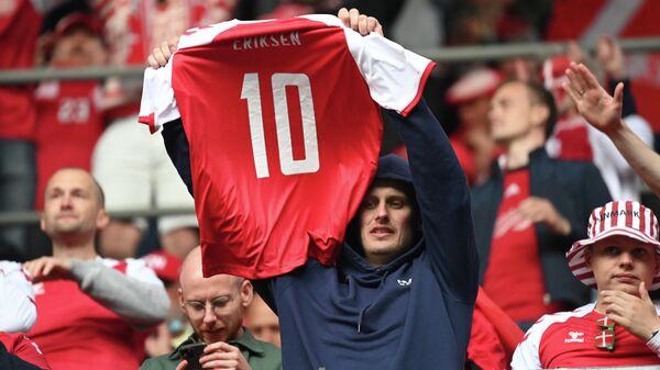 Болельщик сборной Дании держит футболку с номером Кристиана Эриксена
