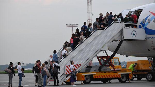 Пассажиры поднимаются на борт самолета на взлетно-посадочной полосе аэропорта Домодедово