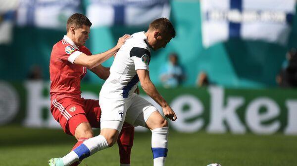 Игрок сборной России Роман Зобнин (слева) в матче 2-го тура группового этапа чемпионата Европы по футболу 2020 между сборными Финляндии и России.