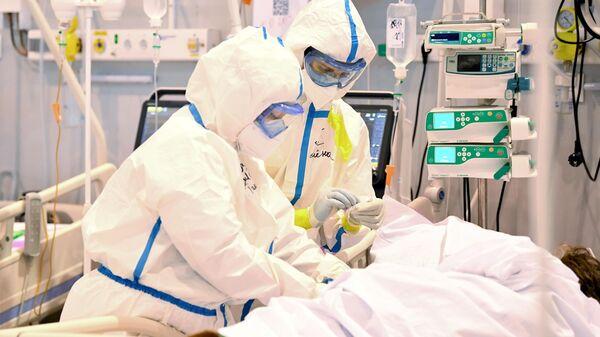 Медицинские работники в палате реанимации и и пациент в палате интенсивной терапии во временном госпитале COVID-19 на ВДНХ в Москве