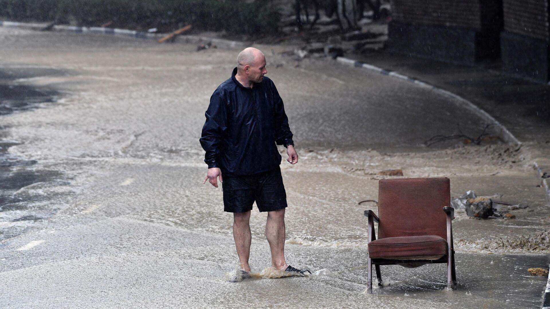 Мужчина на одной из улиц Ялты. В Крыму прошли сильные дожди, вызвавшие подтопления - РИА Новости, 1920, 21.06.2021
