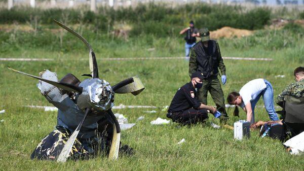 Сотрудники Следственного комитета России и правоохранительных органов работают на месте крушения самолета Л-410 в Кемеровской области