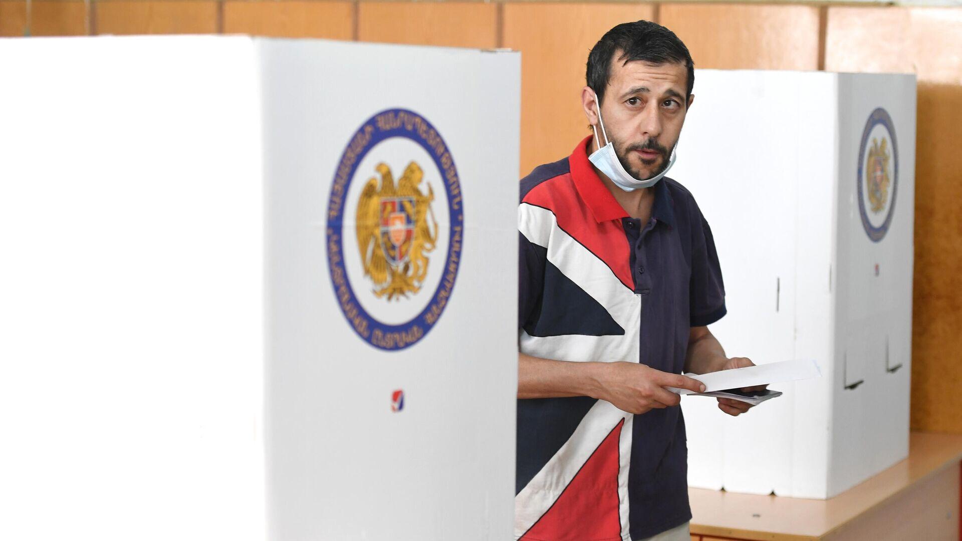 Мужчина на одном из избирательных участков во время досрочных парламентских выборов в Армении - РИА Новости, 1920, 20.06.2021