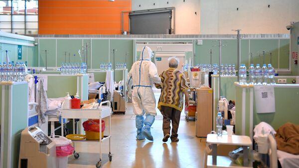Медицинский работник и пациент в палате интенсивной терапии во временном госпитале COVID-19 на ВДНХ в Москве